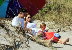 Young couple with baby on beach, advent image 4